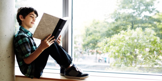 Boy reading book sitting in window nook